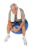 Happy senior man with water bottle sitting on fitness ball. Portrait of a happy senior man with water bottle sitting on fitness ball over white background Stock Image