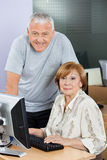 Happy Senior Man And Woman At Computer Desk In Classroom Stock Photo
