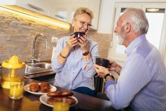 Senior man and woman couple sitting together at home smiling and drinking tea or coffee royalty free stock photo
