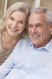 Happy Senior Man & Woman Couple Smiling at Home. Happy senior men and women couple sitting together at home smiling and happy stock photo