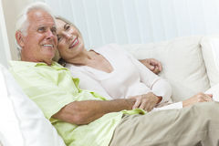 Happy Senior Man & Woman Couple Smiling at Home. Happy senior men and women couple sitting together at home smiling and happy royalty free stock photography
