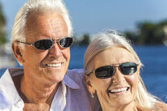Happy Senior Man Woman Couple Tropical Sea. Happy senior men and women romantic couple together looking out to tropical sea or river wearing sunglasses Royalty Free Stock Images