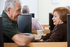 Happy Senior Man And Woman Sitting In Computer Class Stock Photography