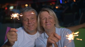 Happy senior man and woman with sparklers. Slow motion of senior couple with Bengal lights sitting outdoor at night. They waving with sparklers and smiling stock footage