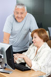 Happy Senior Man With Woman Using Computer In Classroom Stock Images