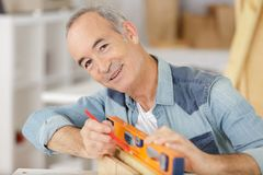 Happy senior man working with level rule. Happy senior man is working with level rule royalty free stock photos