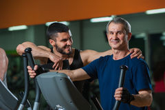 Happy senior man working with personal trainer. Happy smiling senior men working with personal trainer in gym. Male adult exercising on elliptical machine with royalty free stock image