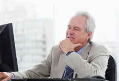 Happy senior manager working with a monitor Royalty Free Stock Image
