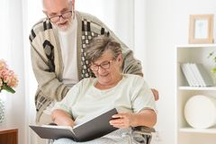 Happy Senior married couple with photo album at nursing home stock images
