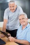 Happy Senior Men With Clipboard In Computer Class. Portrait of happy senior men with clipboard at desk in computer class Stock Photos