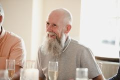 Senior Man At A Wedding. Happy senior men at a wedding. He is sitting at a table, laughing with guests out of the frame royalty free stock photo