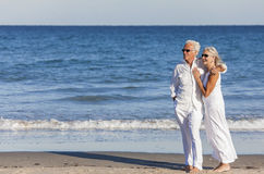 Happy Senior Couple Embracing on Tropical Beach. Happy senior men and women couple together embracing by sea on a deserted tropical beach with bright clear blue Royalty Free Stock Photography
