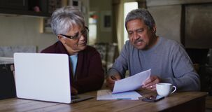 Happy senior mixed race couple doing paaperwork and using laptop