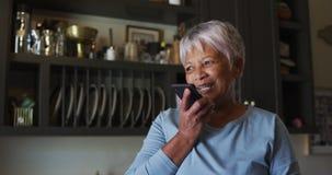 Happy senior mixed race woman talking on smartphone in kitchen