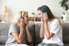 Happy senior mother and adult daughter listening music in headph. Happy senior mother and adult daughter laughing listening to music in wireless earphones stock image