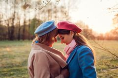 Senior mother and her adult daughter hugging in spring forest. Mother`s day concept. Family values stock images