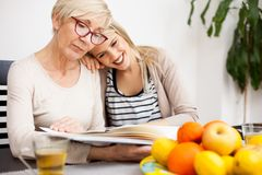 Happy senior mother and her daughter looking at family photo album while sitting at a dining table. Daughter`s head resting on mot. Her shoulder. Happy family royalty free stock photography