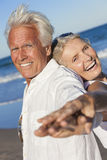 Happy Senior Old Couple on Tropical Beach. Happy senior men and women couple together laughing back to back by blue sea on a deserted tropical beach with bright Stock Photography