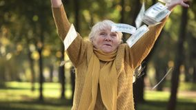 Happy senior old lady throwing stack of dollar bills in park, planned retirement stock photography
