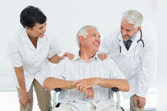 Happy senior patient with doctors sitting in wheelchair Stock Photos