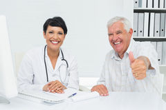 Happy senior patient gesturing thumbs up with doctor Royalty Free Stock Photos
