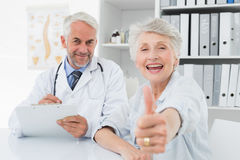 Happy senior patient gesturing thumbs up with doctor Stock Photo
