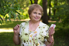 Happy senior pensioner having fun with mobile and headphones Royalty Free Stock Image