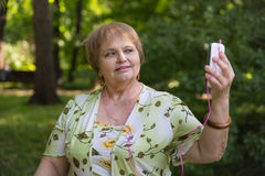 Happy senior pensioner having fun with mobile and headphones Stock Image
