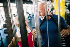 Happy senior people doing exercises in gym to stay fit stock photos