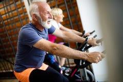 Happy senior people doing indoor biking in a fitness club stock photo