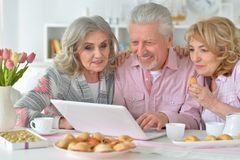 Happy senior people with laptop drinking tea Stock Images