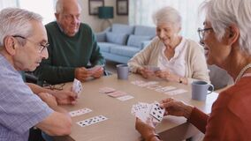 Senior friends playing cards together at nursing home