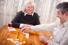 Happy senior people in retirement home playing domino game Royalty Free Stock Photography