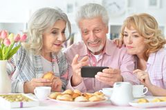 Happy senior people with smartphone drinking tea. At kitchen stock images