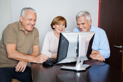 Happy Senior People Using Computer At Desk. Happy senior women with male classmates using computer at desk in classroom Stock Photography