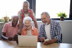 Happy senior people using technology at nursing home. Happy senior people using technology while sitting at table against window in nursing home Stock Image