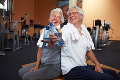 Happy senior people with water. Two happy senior people in a gym drinking water Stock Image