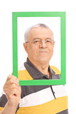 Happy senior posing behind a green picture frame Stock Images