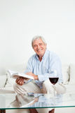 Happy senior reading book. Happy senior man reading a bestseller book on couch Stock Photos