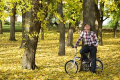 Senior and his bicycle in autumn park. Royalty Free Stock Photo