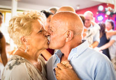 Happy senior retired couple having fun on dancing at restaurant Stock Photos
