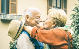 Happy senior retired couple having fun kissing outdoors at travel time. Happy senior retired couple having fun kissing outdoors at travel vacation - Love concept stock photography