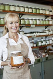 Happy senior salesperson with jar looking away in spice store stock photos