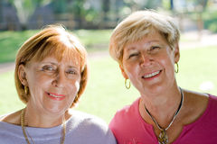 Happy senior sisters & friends. Portrait of two senior caucasian elegant women pose in the park on a sunny day. they are sisters and best friends royalty free stock photo