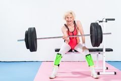 happy senior sportswoman lifting barbell and smiling stock photos