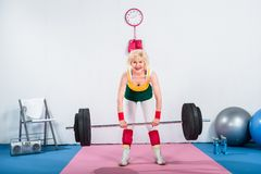 happy senior sportswoman lifting barbell and smiling royalty free stock images