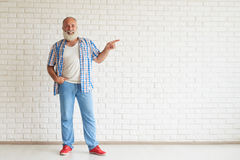 Happy senior is standing and points a finger in the direction Royalty Free Stock Images