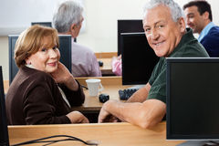 Happy Senior Students Sitting At Desk In Computer Class Royalty Free Stock Photo
