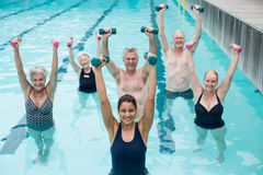 Happy senior swimmers with trainer during weightlifting training in swimming pool Royalty Free Stock Photos