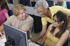 Happy Senior Teacher Assisting Students. During computer class stock images